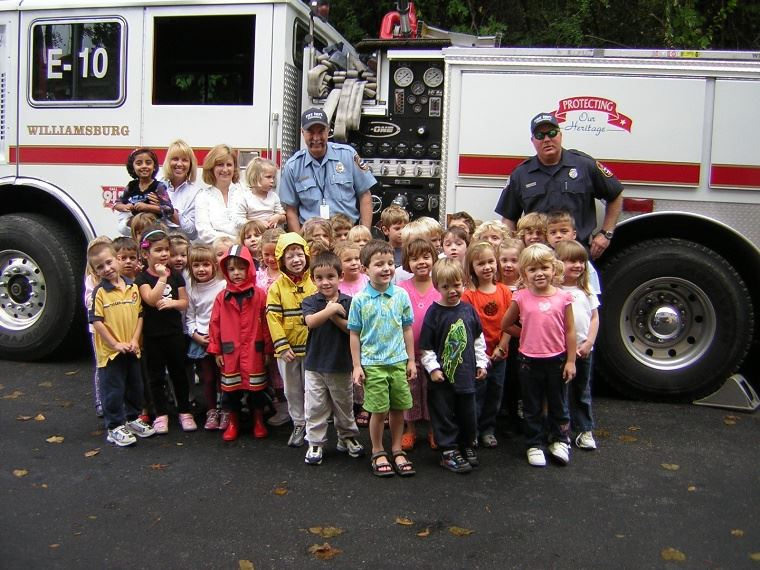 A Group of Children Standing with Firefighters and a Fire Engine